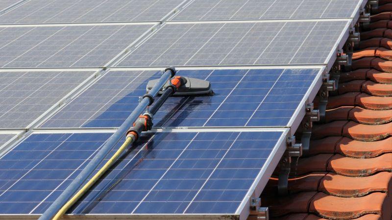 Photovoltaikanlage auf dem Dach: ein Solarmodul wird mit einem speziellen Gerät von Staub befreit.