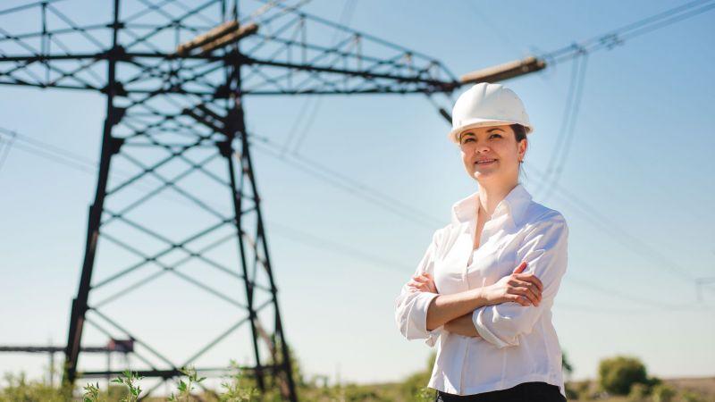 Symbolbild: Eine Ingenieurin steht vor einem Strommast.
