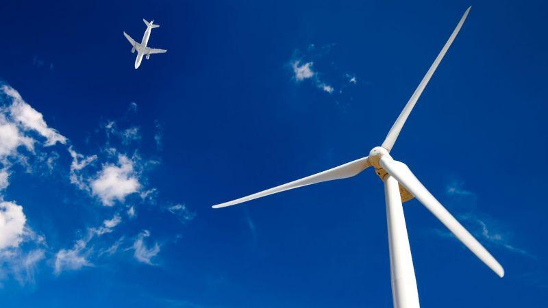 Symbolbild eines Windrads vor einem Flugzeug am Himmel