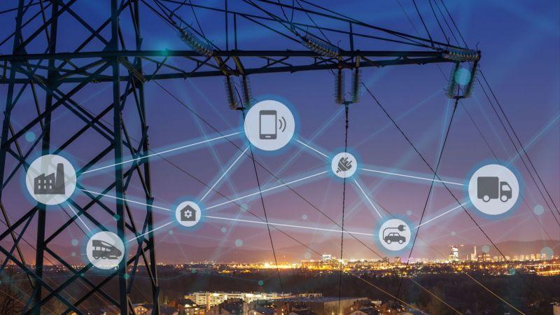 Symbolbild: Strommast eines Höchstspannungsnetzes vor der beleuchteten Skyline einer Stadt