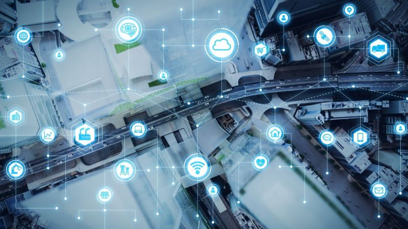 Symbolbild: Die Grafik zeigt aus der Vogelperspektive zeigt eine intelligente Stadt, in der etwa Gebäude und Fahrzeuge miteinander vernetzt sind.