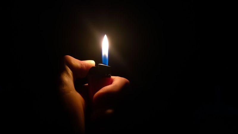 Symbolbild: Daumen einer Hand entzündet ein Feuerzeug vor dunklem Hintergrund