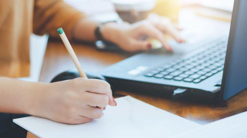 Symbolbild: Nahaufnahme der Hände einer Frau, die vor einem Laptop sitzt. Mit der linken Hand bedient sie den Laptop, mit der rechten schreibt sie.