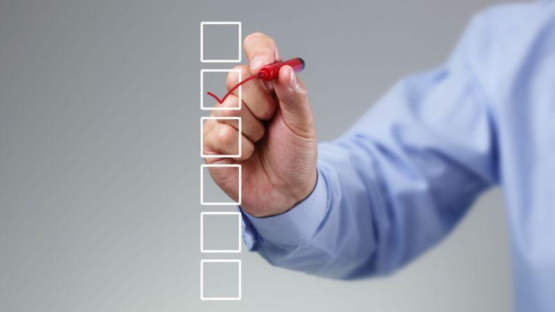 Symbolbild: Nahaufnahme einer Hand, die Checkliste abhakt