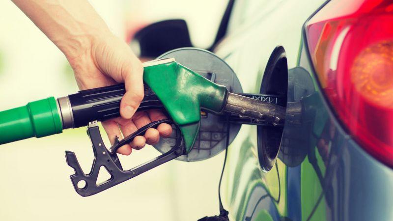 Tankvorgang: Person steckt Tankpistole in ein Auto