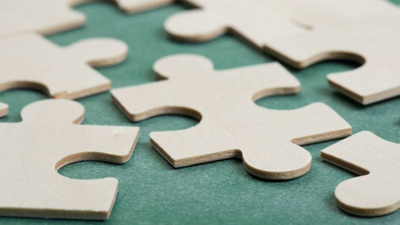 Puzzleteile aus Holz auf grünem Untergrund. Teilweise sind die Puzzlestücke zusammen, teilweise nicht.