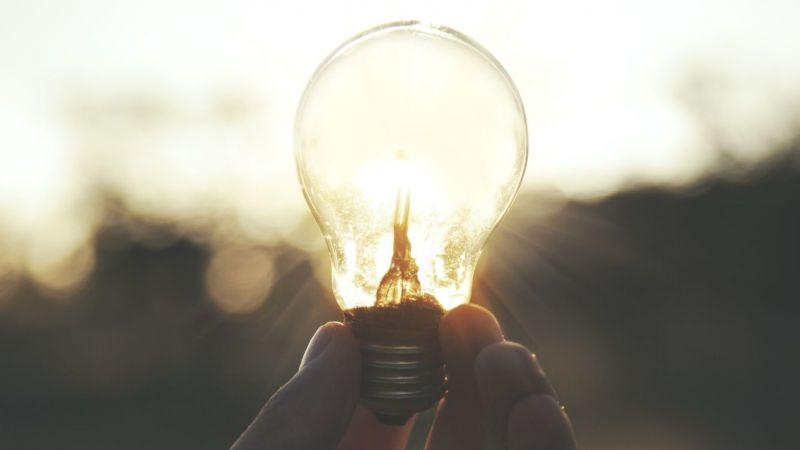 Hand hält Glühbirne fest (Symbolbild)