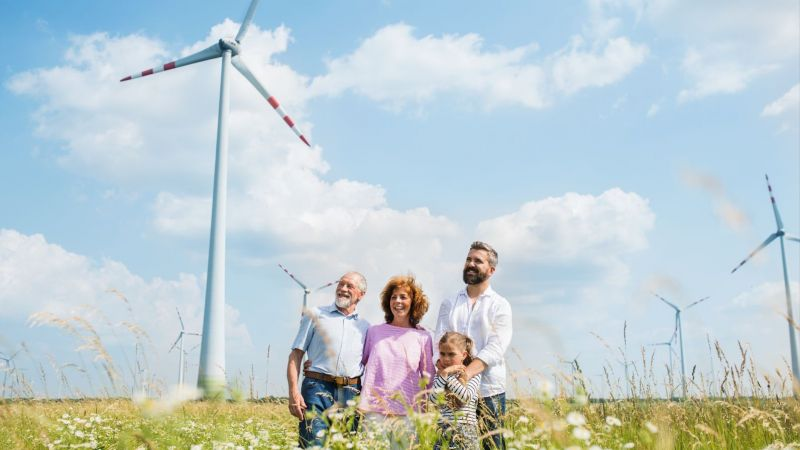 Familie auf einem Feld vor Windrädern