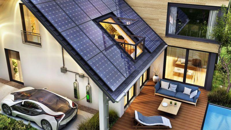 Elektro-Auto lädt vor modernem Haus mit Solardach