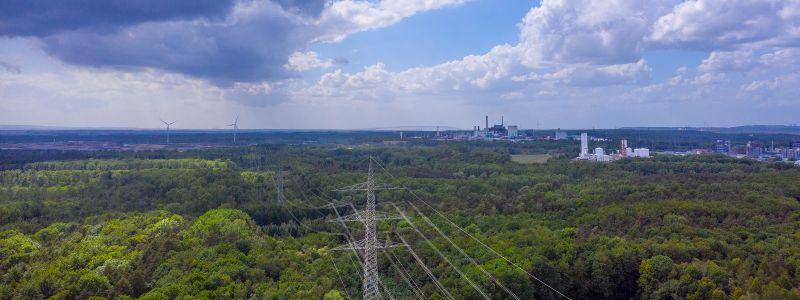 Die Luftaufnahme zeigt eine Stromtrasse, die durch einen Wald führt. Im Hintergrund sind Windräder und Industriefabriken zu sehen.
