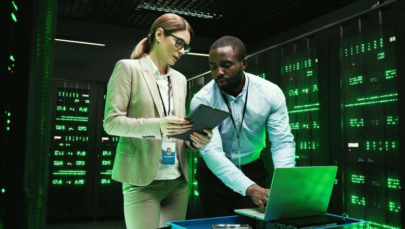 Eine Frau und ein Mann schauen arbeiten an einem Laptop in einem Server-Raum.