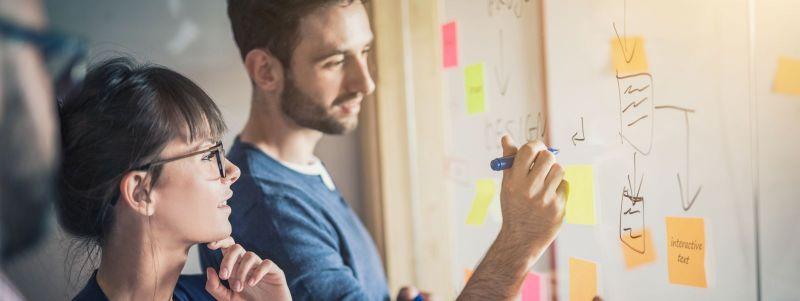 Menschen arbeiten im Team an kreativen Lösungen vor einer Tafel