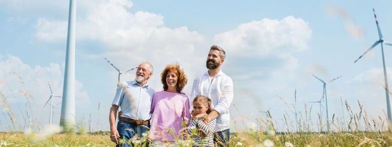 Familie auf Feld mit Windrädern