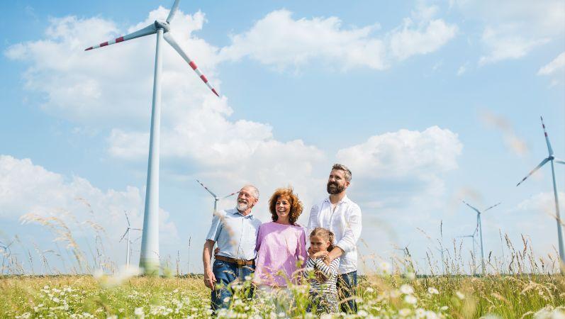 Familie in Feld mit Windrädern (Symbolbild)