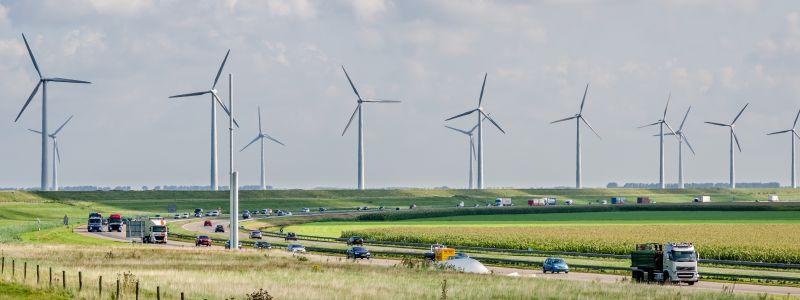 Bundesstraße mit viel Verkehr und Windenergieanlagen im Hintergrund