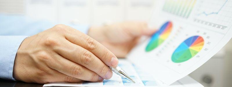 Analyse von verschiedenen Daten, Tabellen und Grafiken auf einem Blatt Papier